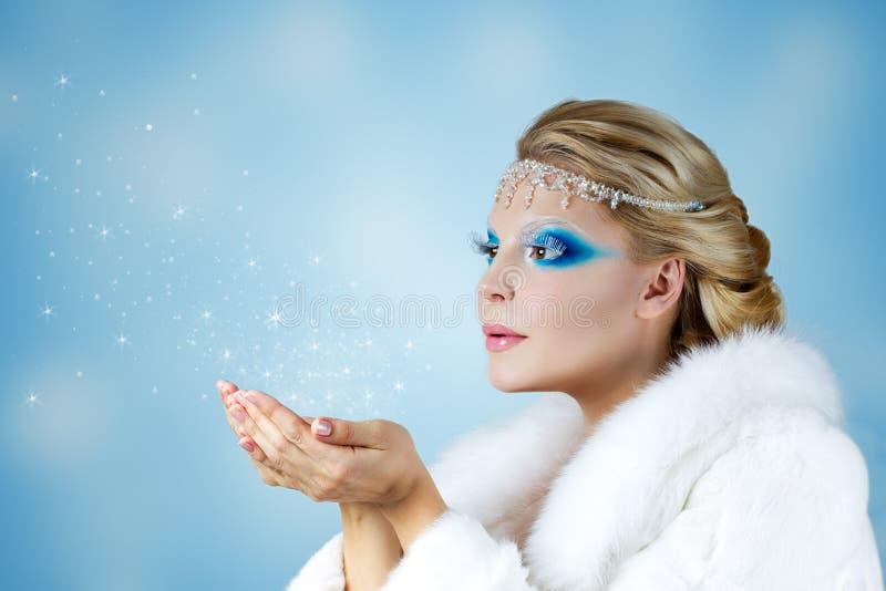 Härlig kvinna som blåser snö fotografering för bildbyråer