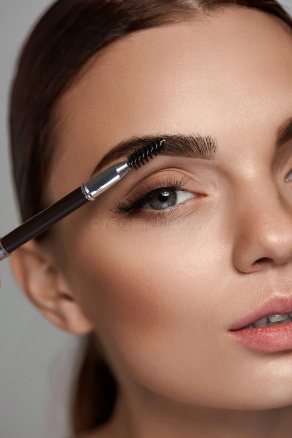 Härlig kvinna som borstar ögonbryn med borsten _ arkivbild