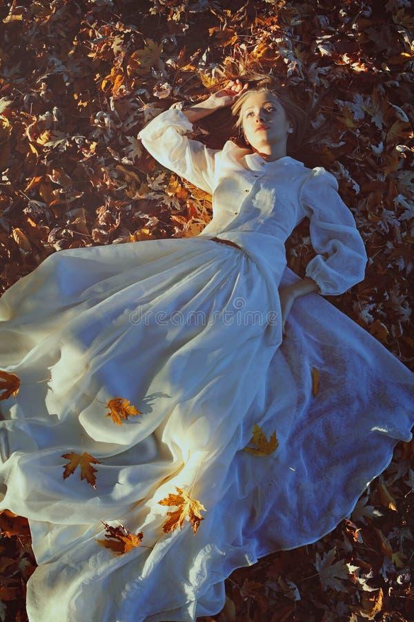 Härlig kvinna som dagdrömmer på en säng av sidor royaltyfri fotografi