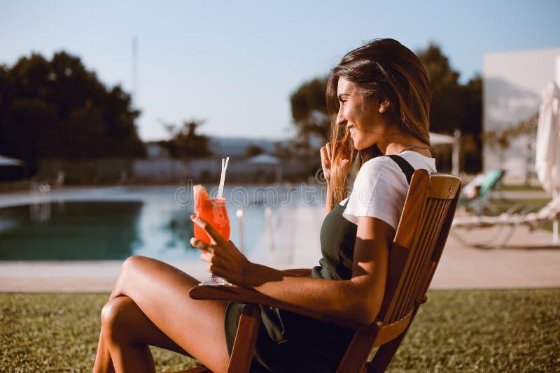 Härlig kvinna som dricker coctailen nära pölen arkivfoto