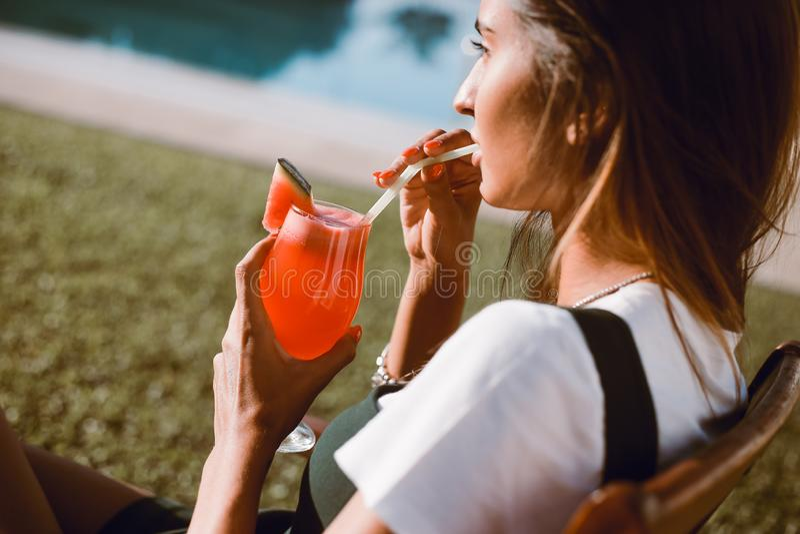Härlig kvinna som dricker coctailen nära pölen arkivbild
