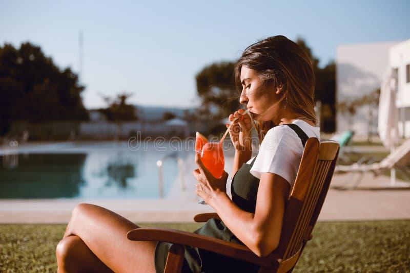 Härlig kvinna som dricker coctailen nära pölen royaltyfri bild