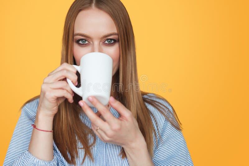 Härlig kvinna som dricker från koppen i studio fotografering för bildbyråer