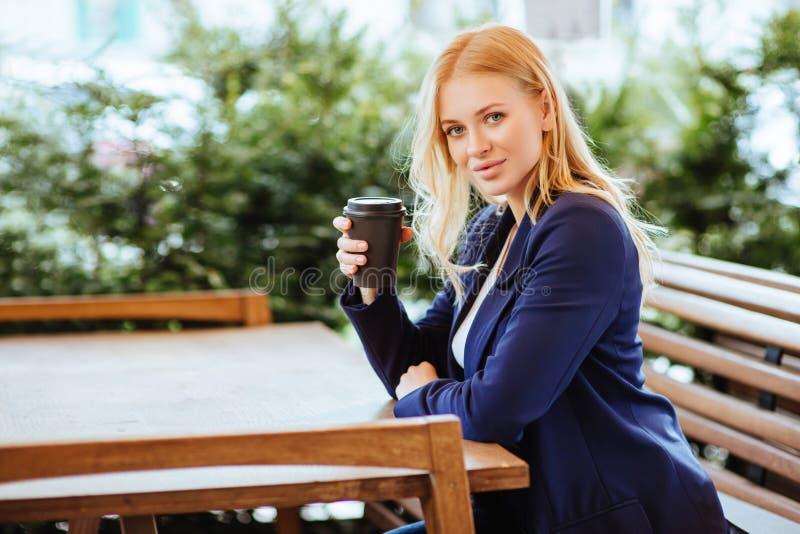 Härlig kvinna som dricker kaffe i ett kafé arkivbilder