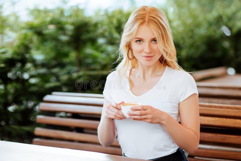 Härlig kvinna som dricker kaffe i ett kafé royaltyfri foto