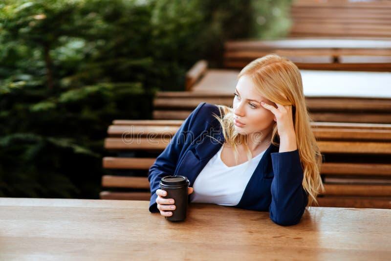 Härlig kvinna som dricker kaffe i ett kafé arkivbild