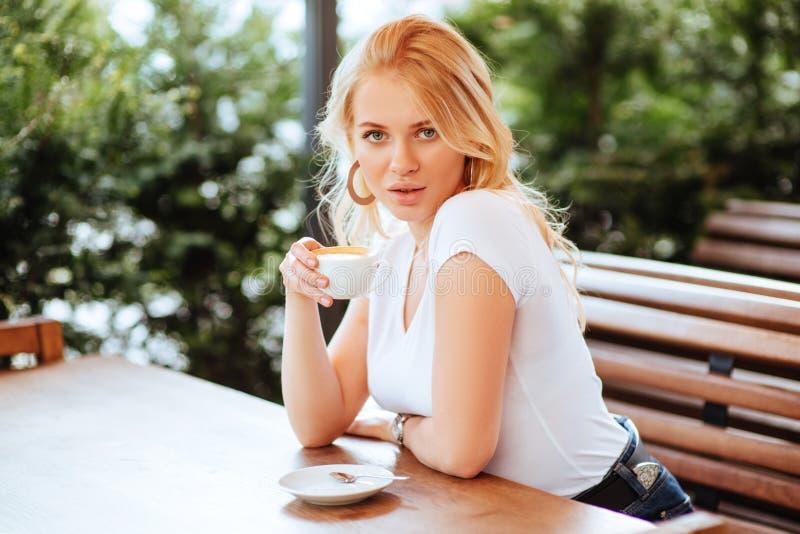 Härlig kvinna som dricker kaffe i ett kafé royaltyfria foton