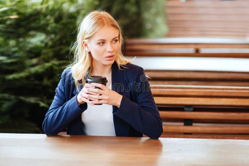 Härlig kvinna som dricker kaffe i ett kafé arkivfoto