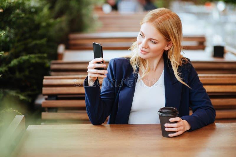 Härlig kvinna som dricker kaffe i ett kafé och en telefon arkivbild