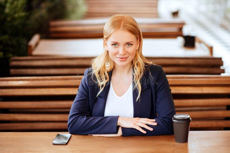 Härlig kvinna som dricker kaffe i ett kafé och en telefon fotografering för bildbyråer