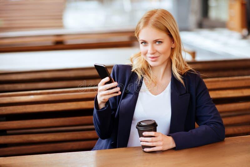 Härlig kvinna som dricker kaffe i ett kafé och en telefon arkivfoto