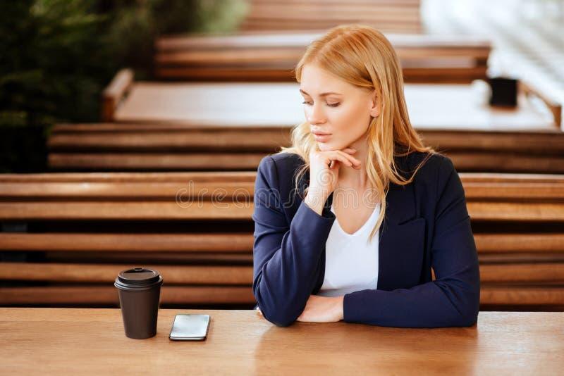 Härlig kvinna som dricker kaffe i ett kafé och en telefon royaltyfria foton