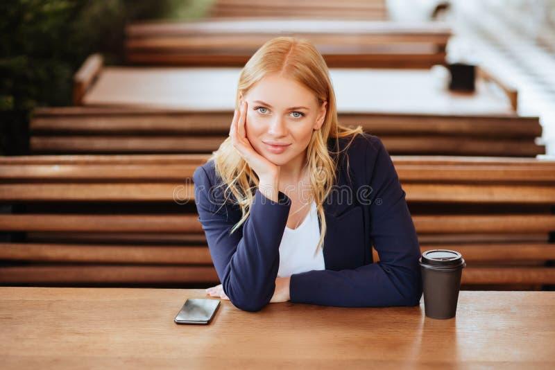 Härlig kvinna som dricker kaffe i ett kafé och en telefon arkivbilder
