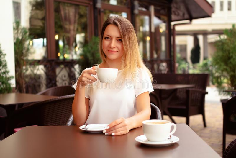 Härlig kvinna som dricker kaffe på kafét arkivbilder