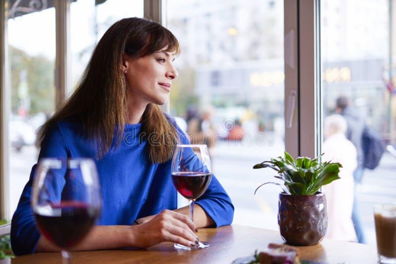 Härlig kvinna som dricker rött vin med vänner i restaurangen, stående med vinexponeringsglas nära fönster Begrepp för kallferiest fotografering för bildbyråer
