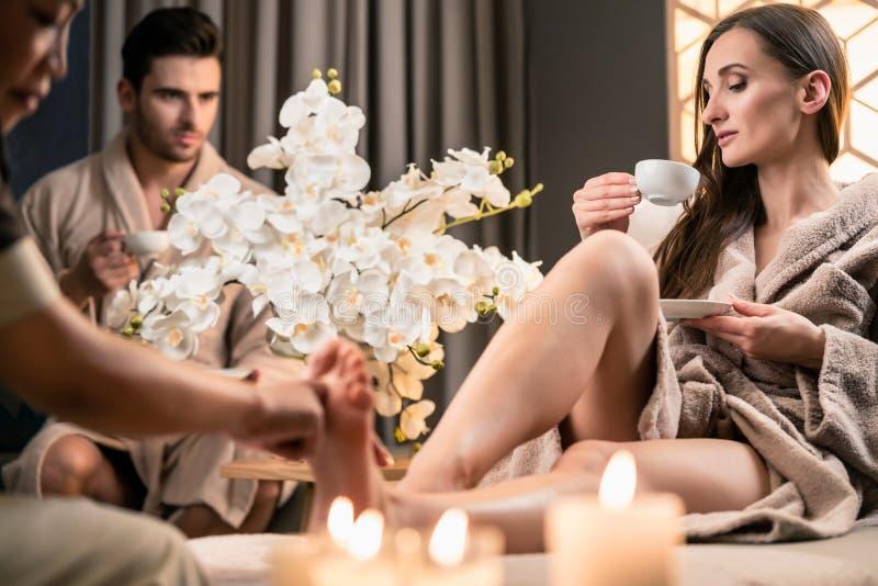Härlig kvinna som dricker te under terapeutisk fotmassage royaltyfri fotografi
