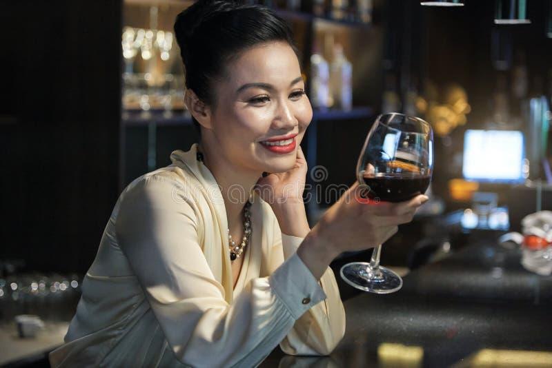 Härlig kvinna som dricker vin arkivfoto