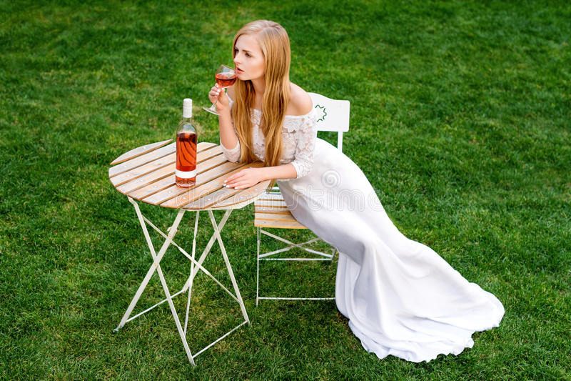 Härlig kvinna som dricker vin i det friakafé Stående av ung blond skönhet i vingårdarna som har gyckel som tycker om a arkivfoto