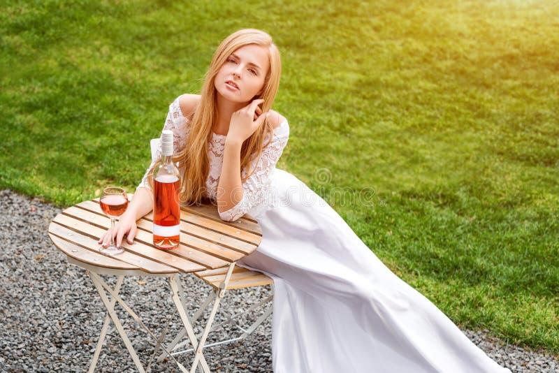 Härlig kvinna som dricker vin i det friakafé Stående av ung blond skönhet i vingårdarna som har gyckel som tycker om a fotografering för bildbyråer