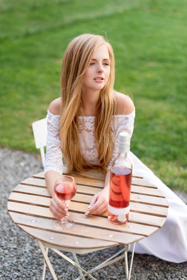 Härlig kvinna som dricker vin i det friakafé Stående av ung blond skönhet i vingårdarna som har gyckel som tycker om a royaltyfri fotografi