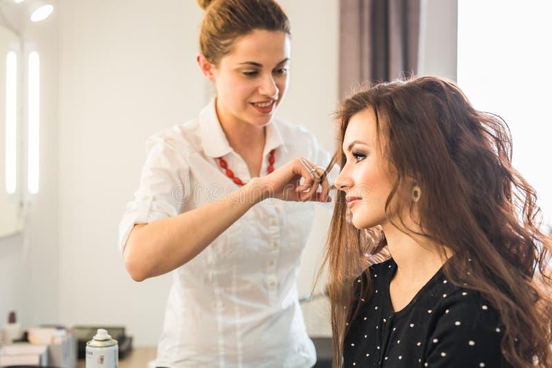 Härlig kvinna som får frisyr av frisören i skönhetsalongen arkivbild