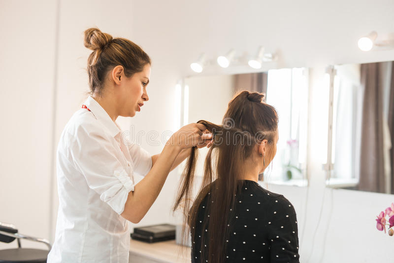 Härlig kvinna som får frisyr av frisören i skönhetsalongen fotografering för bildbyråer