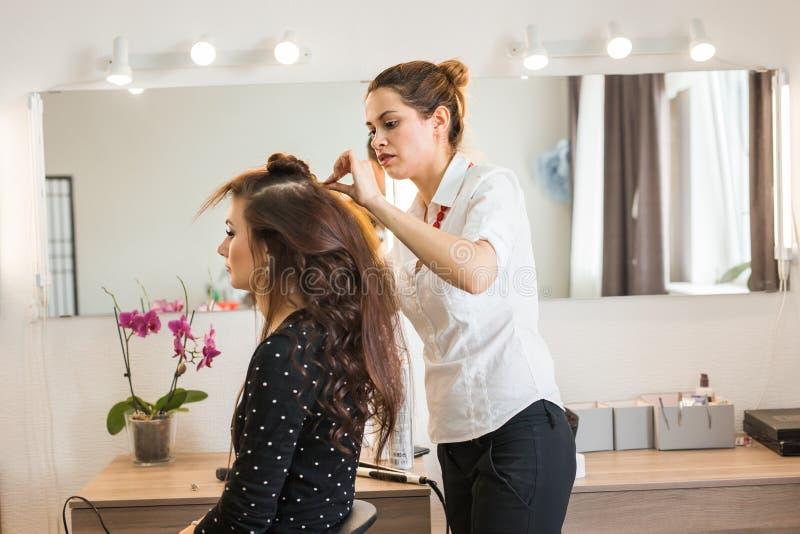 Härlig kvinna som får frisyr av frisören i skönhetsalongen royaltyfri bild