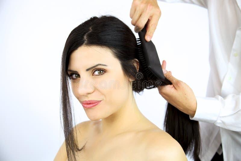 Härlig kvinna som får hår borstat av stylisten royaltyfria bilder