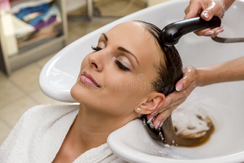 Härlig kvinna som får hårwash i en hårsalong royaltyfri foto