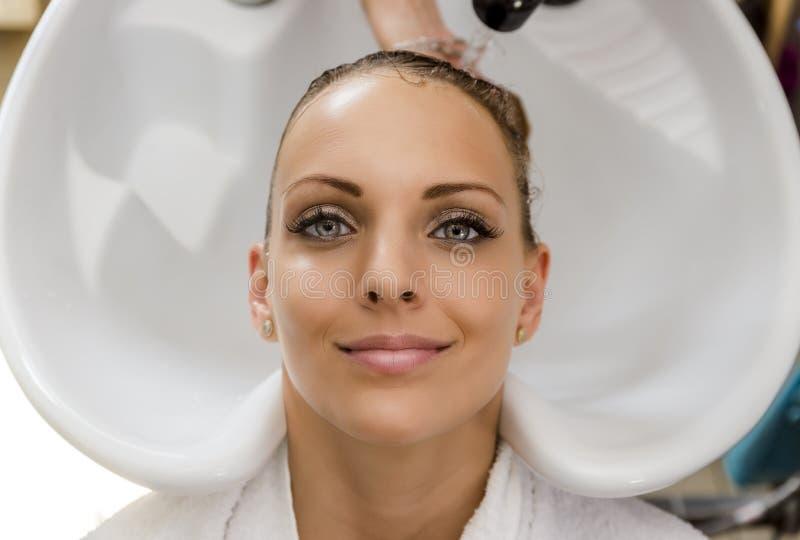 Härlig kvinna som får hårwash i en hårsalong royaltyfria bilder