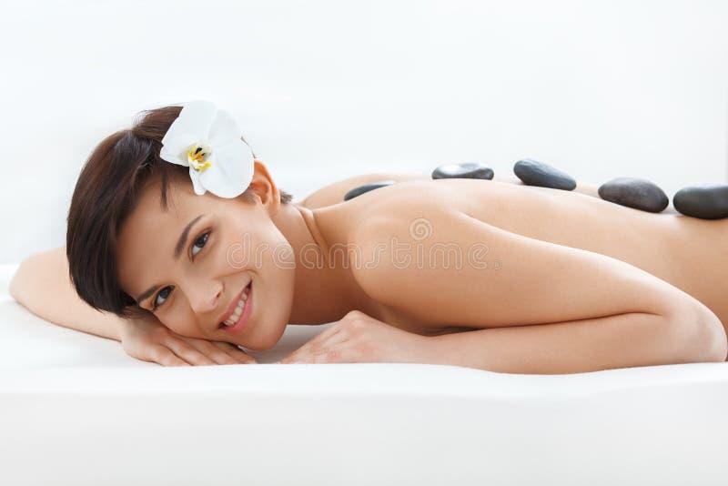 Härlig kvinna som får Spa varm stenmassage Härlig kvinna som får Spa varm stenmassage arkivbild