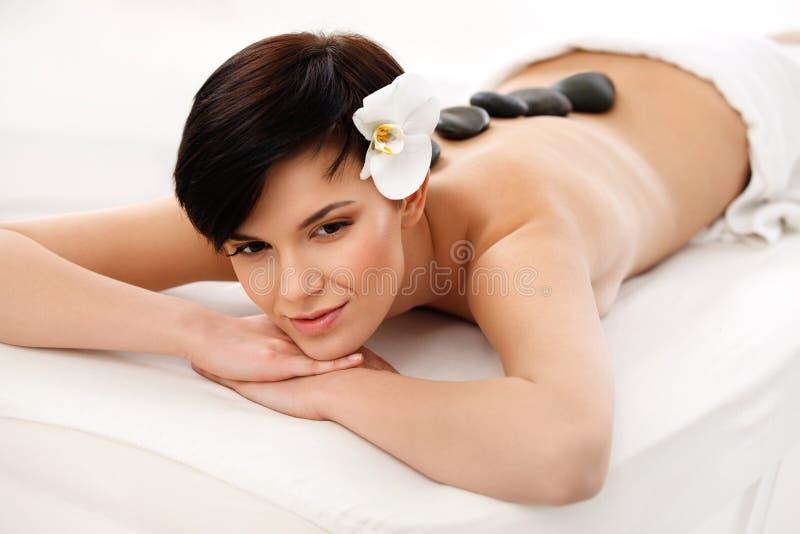 Härlig kvinna som får Spa varm stenmassage Härlig kvinna som får Spa varm stenmassage royaltyfri fotografi