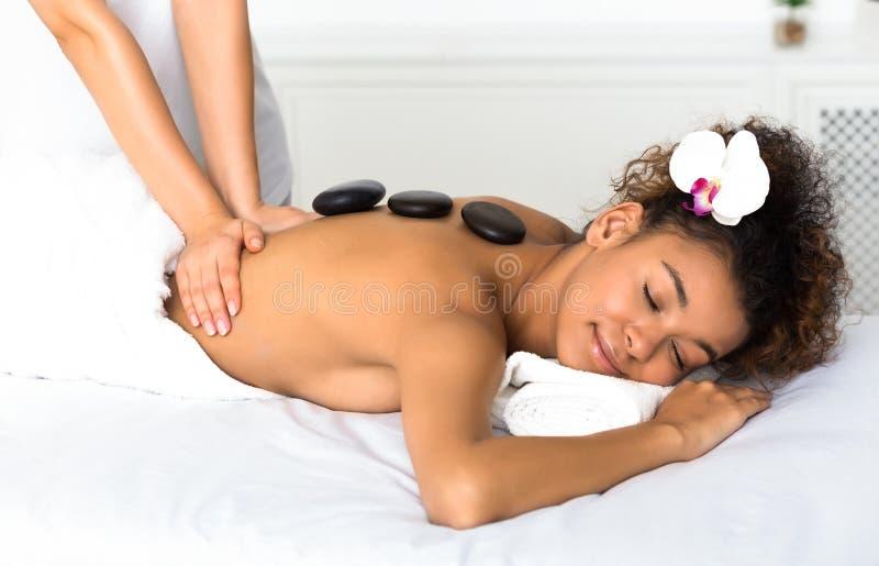 Härlig kvinna som får Spa varm stenmassage Yrkesmässig kosmetolog som masserar kvinnligbaksida arkivfoto