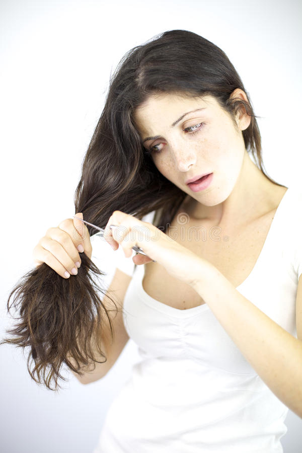 Härlig kvinna som försöker att klippa henne långt hår arkivfoton
