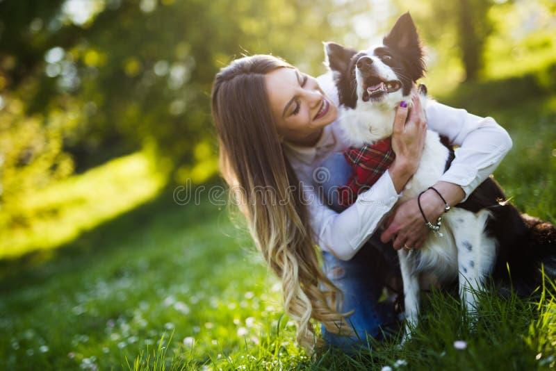 Härlig kvinna som går den gulliga hunden i natur royaltyfria bilder