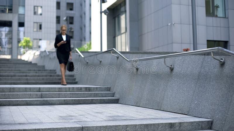 Härlig kvinna som går ner trappa och kontrollerar post på smartphonen, upptaget liv royaltyfri fotografi