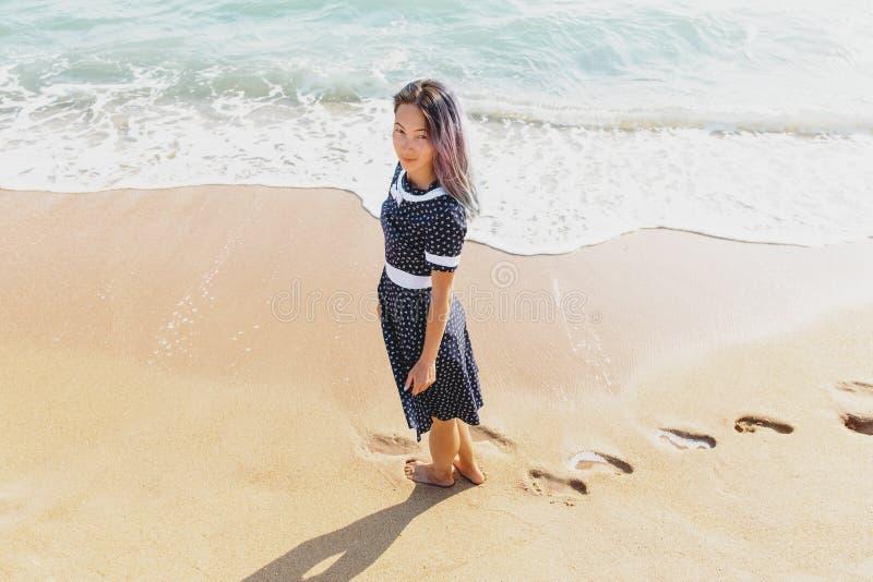 Härlig kvinna som går på sandstranden fotografering för bildbyråer