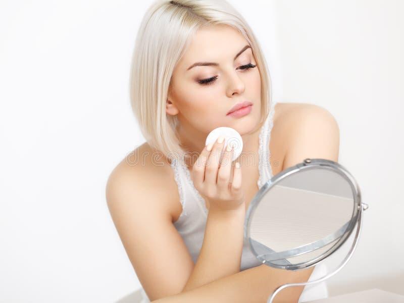 Härlig kvinna som gör daglig makeup. royaltyfri fotografi