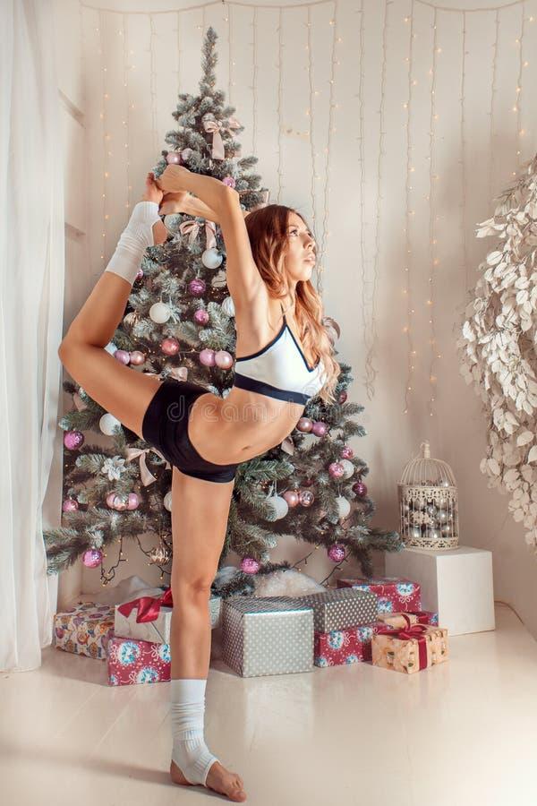 härlig kvinna som gör yoga på julbakgrund arkivbilder