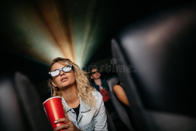 Härlig kvinna som håller ögonen på filmen 3d i teater arkivbild