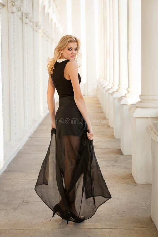 Härlig kvinna som ha på sig den storartade klänningen royaltyfri bild