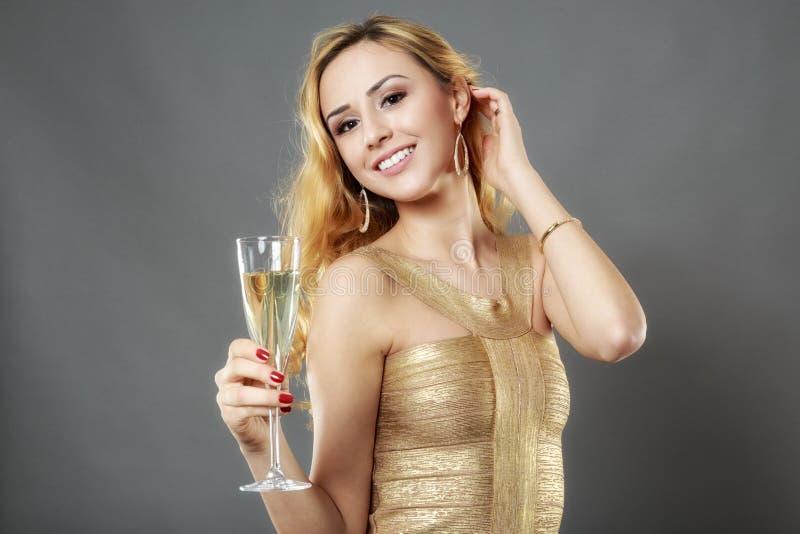 Härlig kvinna som har ett exponeringsglas av champagne royaltyfri fotografi