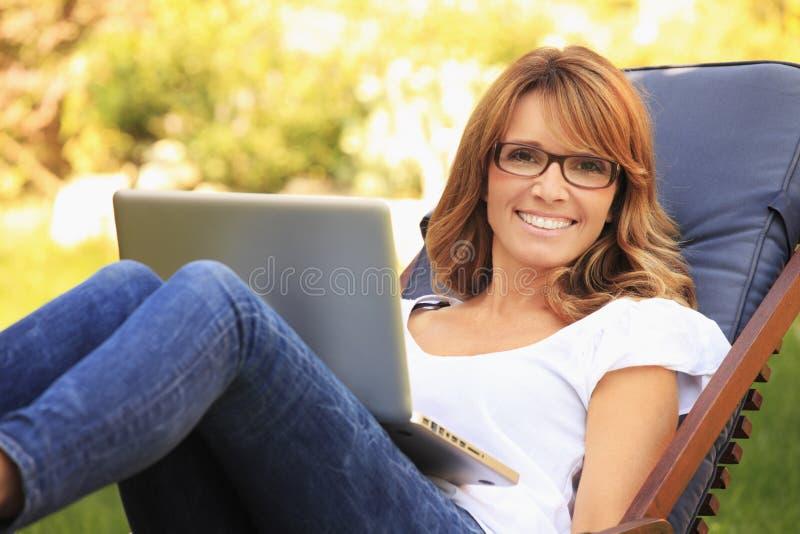 Härlig kvinna som hemma arbetar arkivbild