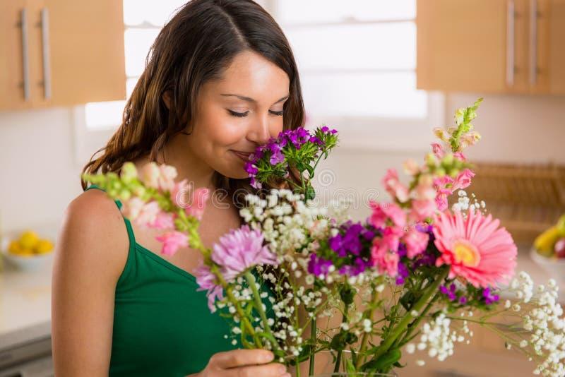 Härlig kvinna som hemma luktar blommor från hennes vän på valentindag arkivbilder
