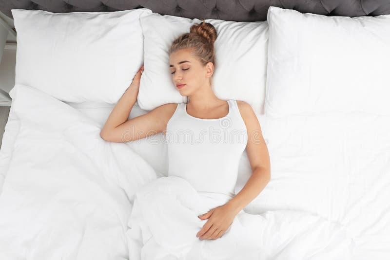 Härlig kvinna som hemma sover på den bekväma kudden i säng arkivbild