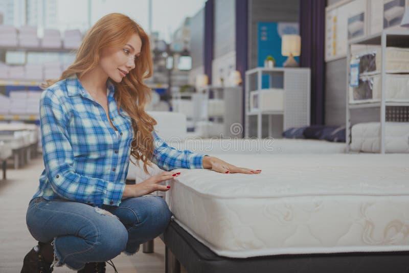 H?rlig kvinna som k?per den nya madrassen p? inredninglagret arkivbild