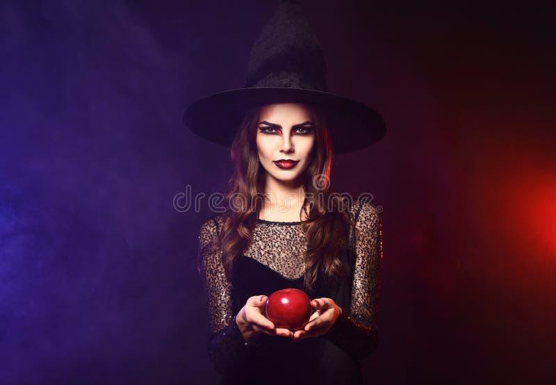Härlig kvinna som kläs som häxan för allhelgonaafton med äpplet på bakgrund för mörk färg arkivfoton