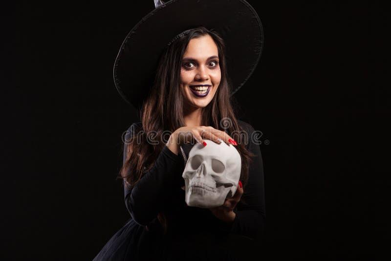 Härlig kvinna som kläs som häxan för allhelgonaaftonen som spelar med en läskig skalle arkivfoto