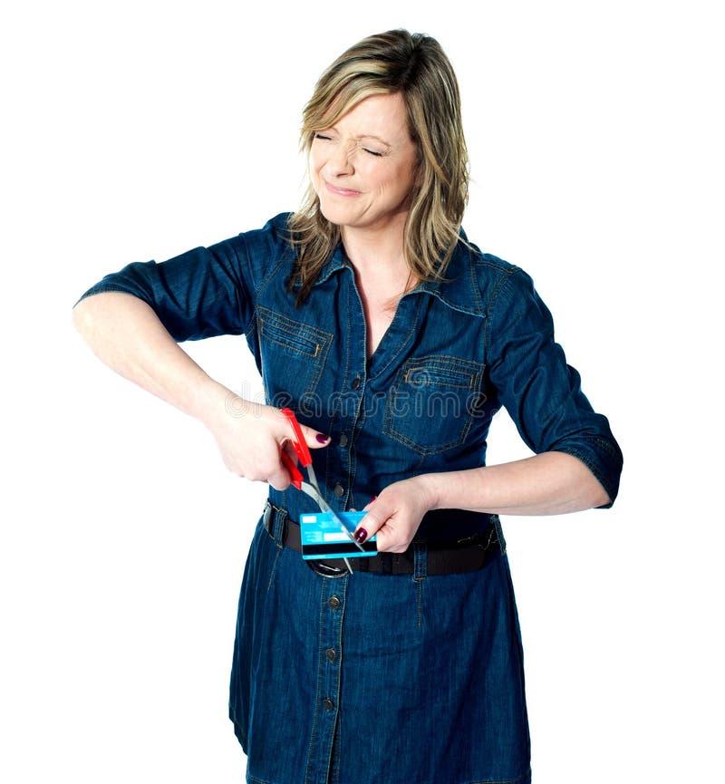 Härlig kvinna som klipper hennes kreditkort arkivbild