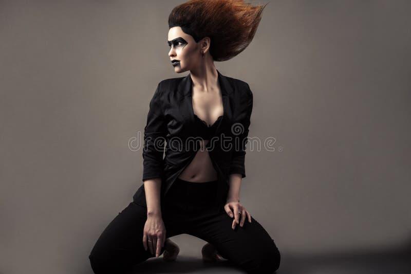 Härlig kvinna som knäfaller med frodig hår- och mörkermakeup royaltyfri fotografi